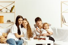 Little girls, attractive young mother and charming grandmother are sitting at home royalty free stock image