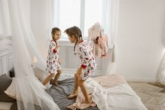Two little girls in their pajamas are having fun jumping on a bed in a sunlit cozy bedroom stock photography