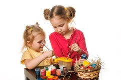 Two little girls to paint Easter eggs on a white background Royalty Free Stock Photo