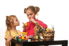 Two little girls to paint Easter eggs on a white background Royalty Free Stock Photos