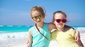 Two little girls together on the beach on caribbean vacation. Portrait of two kids outdoors. Adorable little girls at beach during summer vacation stock footage