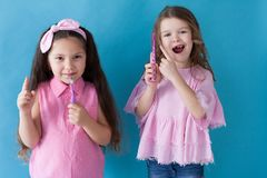 Two little girls with toothbrushes in dentists stock image
