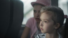 Two little girls travel by bus, look out the windows and admire nature. Traveling in a tourist bus. Two little girls ride in a bus and look out the windows stock video footage