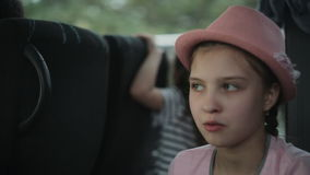 Two little girls travel by bus, look out the windows and admire nature stock video