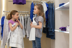 Two little girls try on clothes in a modern store Stock Images
