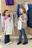 Two little girls try on clothes in a store Stock Image