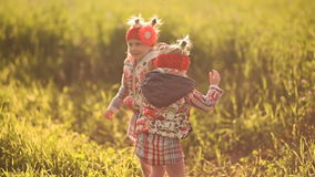 Two little girls, twins frolicking in the green field. stock video