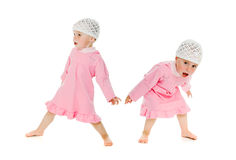 Two little girls twins restless. On the white background Royalty Free Stock Image