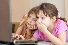 Children using computer. Two little girls using computer stock photo