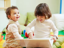 Two little girls using laptop computer. Female toddler and 2-3 years old girl playing with pc in kindergarten. Horizontal shape Royalty Free Stock Image