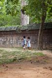 Two little girls walking along a stone wall royalty free stock photography