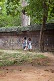Two little girls walking along a stone wall stock photo