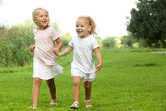 Two little girls walking in the park. Portrait of two little girls walking in the park holding hands stock photos