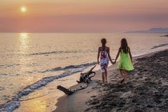 Two little girls walking together on the beach in the sunset Stock Photos