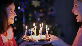 Two little girls is watching to candles on birthday cake. stock video