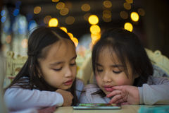 Two little girls watching a video on mobile phone. Two little girl watching a video on a mobile phone in a restaurant Royalty Free Stock Photo