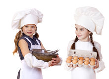 Two little girls in a white apron holding box of raw eggs and bo Stock Photography