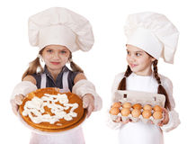 Two little girls in a white apron holding box of raw eggs and pi Royalty Free Stock Photo