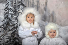 Two little girls in white coats  and white fur hats Royalty Free Stock Image