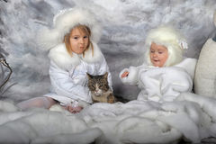 Two little girls in white coats and white fur hats Royalty Free Stock Images