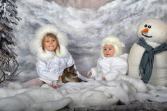 Two little girls in white coats and white fur hats Stock Photos