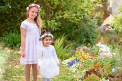Two little girls in white dresses and flower wreath having fun a summer garden. royalty free stock image