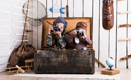 Two little girls in wooden chest playing rarity cameras. Two little girls in hats in big wooden chest playing rarity cameras Royalty Free Stock Photography