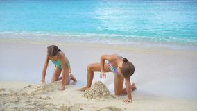 Two little happy girls have a lot of fun at tropical beach playing together with sand. Little girls having fun at tropical beach playing together. Adorable stock footage