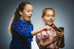 Two little happy girls using mobile or cell phone isolated grey background Royalty Free Stock Photo