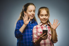 Two little happy girls using mobile or cell phone isolated grey background Stock Photography