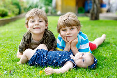 Two little happy kid boys with newborn baby girl, cute sister. Royalty Free Stock Photo