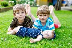 Two little happy kid boys with newborn baby girl, cute sister. Royalty Free Stock Photography