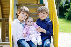 Two little happy kid boys with newborn baby girl, cute sister. Royalty Free Stock Image