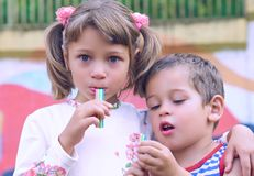 Two little happy kids boy and girl stand in each other`s arms and chewing gum. Siblings on playground in summer or spring in. Kindergarten stock photo