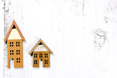 Two little houses on wooden background - investment real estate insurance concept Royalty Free Stock Photos