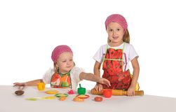 Two little housewifes in colourful aprons Stock Images