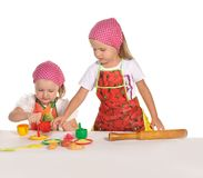 Two little housewifes in colourful aprons Royalty Free Stock Photography