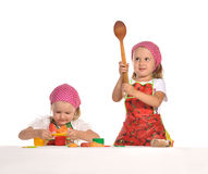 Two little housewifes in colourful aprons Royalty Free Stock Images