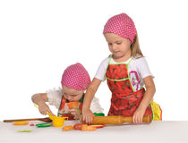 Two little housewifes in colourful aprons Royalty Free Stock Photos