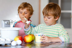 Two little kid boys baking apple cake indoors Royalty Free Stock Photography