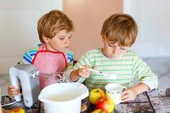 Two little kid boys baking apple cake indoors Royalty Free Stock Image