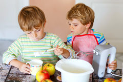 Two little kid boys baking apple cake indoors Stock Photos