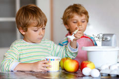Two little kid boys baking apple cake indoors Stock Images