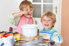 Two little kid boys baking apple cake indoors Royalty Free Stock Image