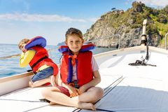Two little kid boys, best friends enjoying sailing boat trip. Family vacations on ocean or sea on sunny day. Children stock photos