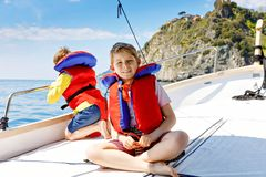 Two little kid boys, best friends enjoying sailing boat trip. Family vacations on ocean or sea on sunny day. Children royalty free stock image