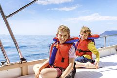 Two little kid boys, best friends enjoying sailing boat trip. Family vacations on ocean or sea on sunny day. Children stock photography