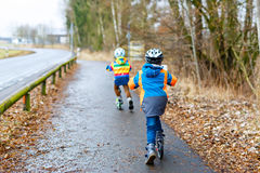 Two little kid boys, best friends riding on scooter in park Royalty Free Stock Photo