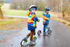 Two little kid boys, best friends riding on scooter in park Royalty Free Stock Image