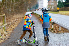 Two little kid boys, best friends riding on scooter in park Royalty Free Stock Photography